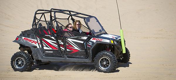 two women in ORV on sand dune