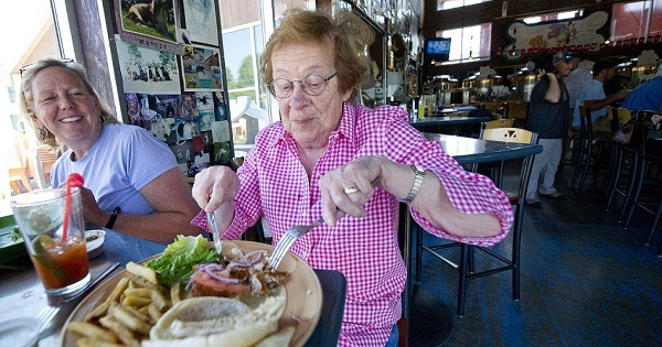 An older woman wearing glasses, cutting up her fresh fish meal with a fork and knife, while another woman looks on