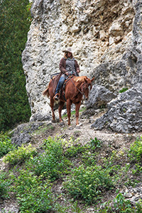 Jenny Cook rides her horse past the Sugarloaf formation on Mackinac Island.