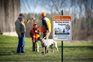 A small group of hunters dressed in fall gear and hunter orange, with a dog, talk in the background; a Hunting Access Program sign in the foreground