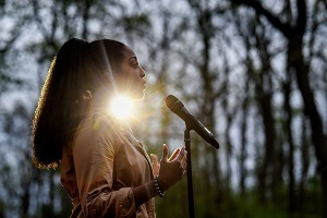 Side view of a ponytailed African American woman speaking into a microphone, outdoors, with the sun shining behind her