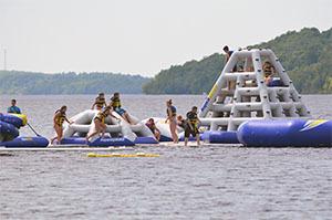 Visitors enjoy inflatable water park at Van Riper State Park