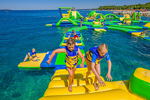 two kids climb on inflatable water park structure
