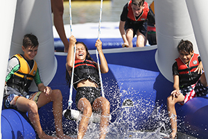 girl swinging on inflatable water park structure
