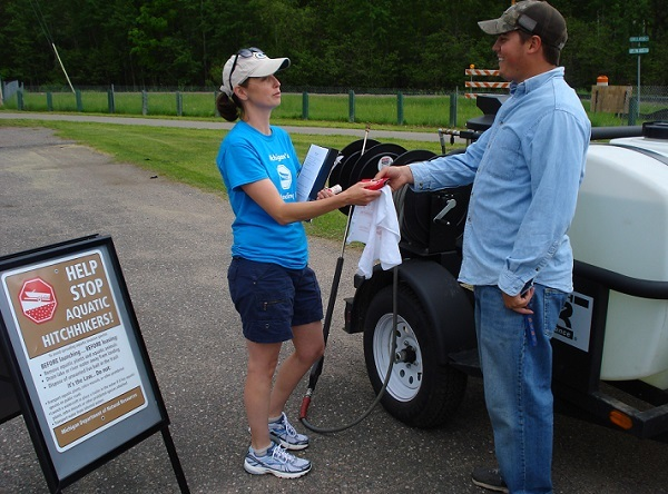 An AIS Lansing Blitz volunteer talks with a boater about simple ways to reduce the spread of aquatic invasive species