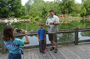 girl taking photo of boy and dad folding up fish on pole