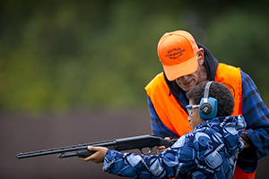 hunter education instructor helps student with target shooting