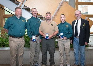 DNR Wildlife Division employees, four men, plus chief Russ Mason, pose holding their lifesaving awards