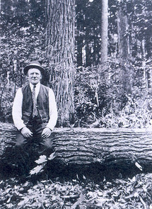 historic photo of Herman Lunden sitting on log in Pigeon River Country State Forest