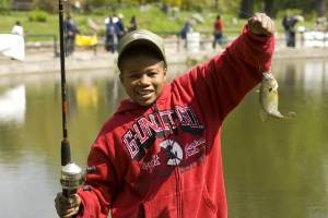 smiling little boy holding a fishing pole in one hand and a fish on the line in the other hand