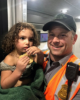 Lt. Brandon Kieft with the Michigan DNR holds Gabriella Vitale at the search and rescue command center.