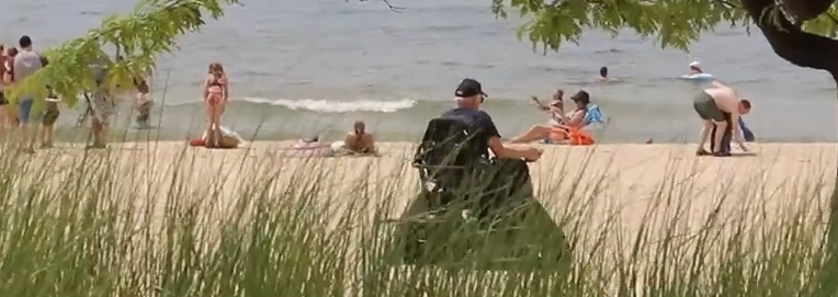 an older man using a wheeled track chair to explore the beach at Muskegon State Park this summer