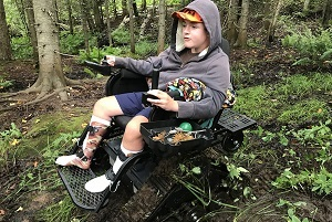 young boy wearing a gray hoodie and shorts, in a track chair, exploring the forest