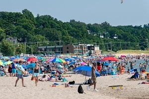 crowded beach on a sunny day at Grand Haven State Park, many umbrellas, visitors, etc.
