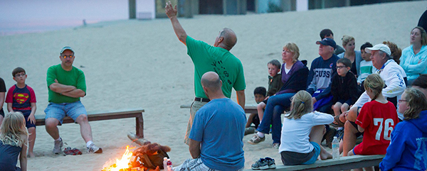 park staffer points to sky as visitors seated around campfire listen