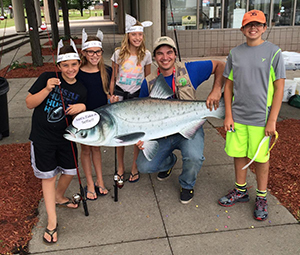 kids in fish hats pose with DNR staffer holding large fish cutout