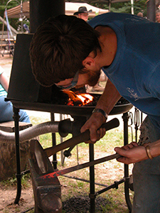 blacksmith pounding hot metal with hammer
