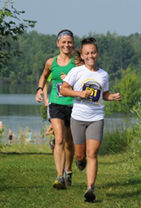 two female runners with lake and woods in background