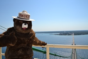 Smokey Bear waving from atop the Mackinac Bridge in the Straits of Mackinac, blue sky in the background