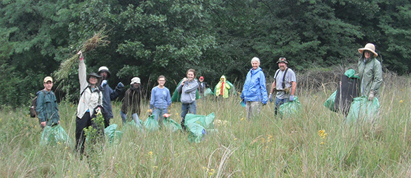 Group of park stewardship volunteers with garbage bags in field