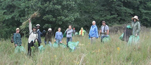 Group of park stewardship volunteers with garbage bags in field