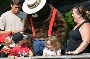 Smokey Bear breaks up the action at the fishing pier with a personal appearance.