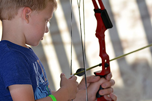 A young archer gets ready to pull the string back on his bow.