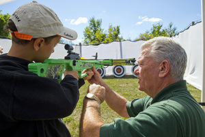 DNR staffer teaching boy to shoot crossbow at target