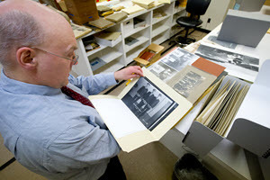A man looks at a photograph in an archival folder.