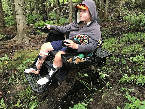 boy in track chair in forest