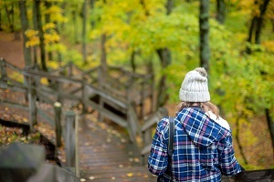 view from behind, a woman wearing flannel and a knit hat, walking down a trail and walkway, surrounded by green forest