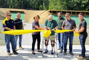 DNR employees and other supporters of the Echo Point Shooting Range gather to cut the ribbon on recent upgrades