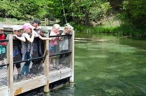 A group of kids leaning against the pier railing, watching the water at Oden State Fish Hatchery