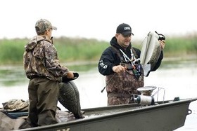 A man and a young boy dressed in hunting gear, standing up in a boat and setting out waterfowl decoys