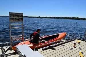 A visitor getting into a kayak on the accessible canoe and kayak launch on Lake Cadillac at William Mitchell State Park