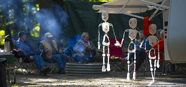 people sitting around campfire at campsite with Halloween decorations