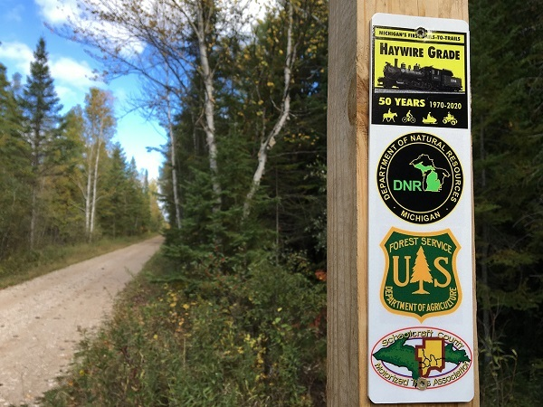 a view of the Haywire Grade trail, with a closeup of partner agency logos on a trail post