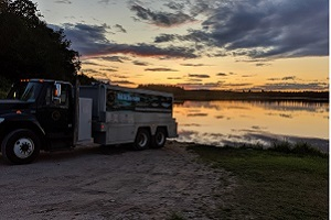 A fish stocking truck backed up to a pond at sunset