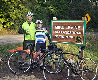 Two bicyclists pose for a photo in front of a sign for the Mike Levine Lakelands Trail State Park in southeast Michigan.