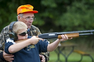 A senior male hunter safety education instructor wearing an orange DNR cap instructs a young boy on proper, safe shooting techniques