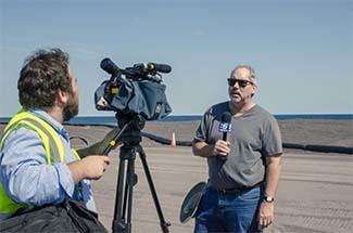 Chris Korleski is interviewed by WLUC-TV6 Houghton Bureau reporter Jake Swope on the stamp sands.