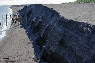 A group of experts tours the deposits of stamp sands along the Lake Superior shoreline in August.