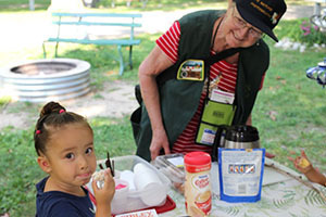 campground host helping kid with art project
