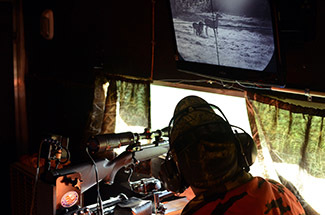 A screen inside one of the hunting trailers shows deer in the crosshairs.