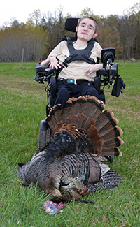 Robbie Ivey shown in his wheelchair with the turkey he shot this year.