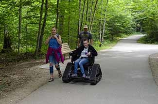 A visitor is shown using a track chair at Tahquamenon Falls State Park.