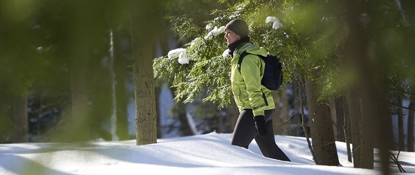 woman dressed in winter gear, hiking through a snowy forest, backlit by the sun