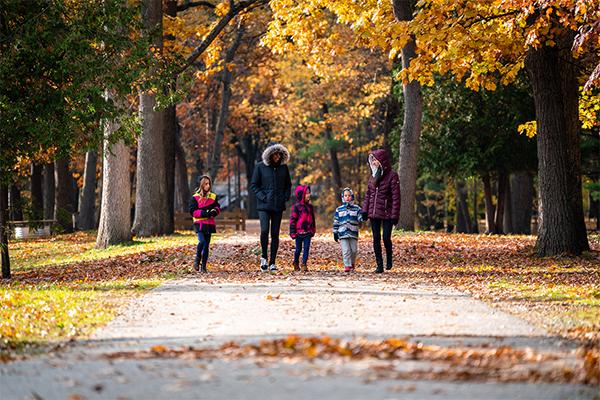 Women and children walk through a pretty autumn scene at a Michigan state park.