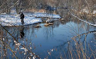 Two men fish along an open river in a wintry scene.
