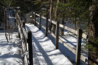 A snow-covered bridge along a hiking trail near Marquette is shown.